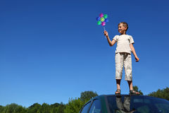 Boy stands on roof of car and holds windmill Stock Image
