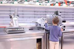 Boy stands at scales in empty shop Royalty Free Stock Image