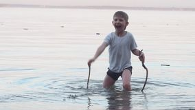 The boy stands in the sea and plays with water sticks in his hands, rejoices and laughs, sticks in the water stock video