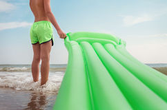 Boy stands on sea surf line with swimming air mattress Royalty Free Stock Photo