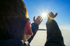 The boy stands on  shore   frozen river and pulled by hand to sun. Stock Images