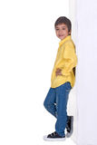 The boy stands and smiles. The boy stands having leaned the elbows to a wall and smiles Royalty Free Stock Images