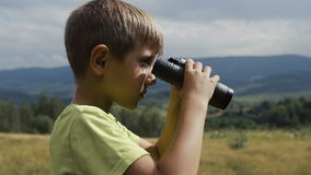 The boy stands on the top of the mountain and looks at the binoculars stock video footage