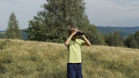 The boy stands on the top of the mountain and looks at the binoculars stock footage