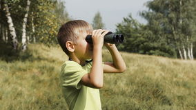 The boy stands on the top of the mountain and looks at the binoculars. Slow motion stock video