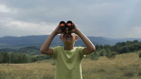The boy stands on the top of the mountain and looks at the binoculars stock video