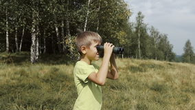 The boy stands on the top of the mountain and looks at the binoculars. Slow motion stock video footage