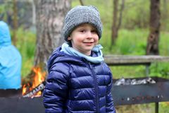 Boy stands in warm clothes and smiles. Child in the country in the cold season. In the background a grill or a bonfire. royalty free stock image