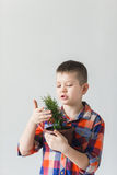 A boy stands on a white background with a plant on Earth Day Royalty Free Stock Images