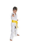 The boy stands in white kimono of the karate with a yellow bel Stock Photos