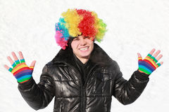 Boy stands in wig of clown and shows bright gloves Royalty Free Stock Photos