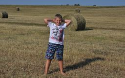 Boy stanging near haystack Royalty Free Stock Photo