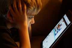 Boy staring at iPad tablet computer. Young boy concentrating on iPad tablet computer with ambient lighting reflecting on his face with shallow focus stock photos