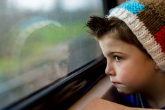 Boy staring through window. A boy in a train staring through a window Royalty Free Stock Images