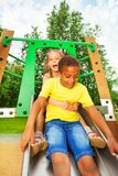 Boy start to slide on chute and girl sit behind Stock Photos