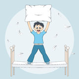 Boy starts pillow fight. Child with cushion on bed Stock Photo