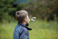 The boy starts up soap bubbles Stock Images