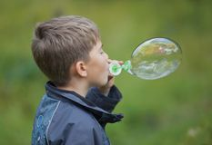 The boy starts up soap bubbles Royalty Free Stock Photos