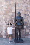 Boy with a statue of a medieval warrior Stock Photography