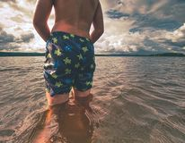Free Boy Stay In Lake With Water Under Knee And Test Temperature Stock Photography - 161187072