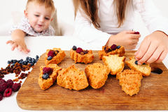 Boy stealing berries while his sister cooking Stock Photography