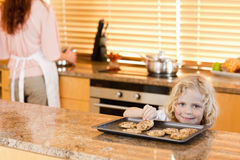 Boy stealing a cookie while his mother is not watching Royalty Free Stock Image