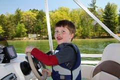 Boy Steering Boat Royalty Free Stock Photo