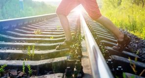 Boy steps over the rails Royalty Free Stock Image