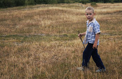 The boy with the stick is on the field Royalty Free Stock Images
