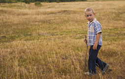 The boy with the stick is on the field Royalty Free Stock Photography