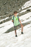 Boy with stick stands on snow in mountains Stock Image