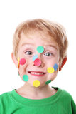 Boy with stickers on his face. A young boy with colorful stickers on his face Royalty Free Stock Images