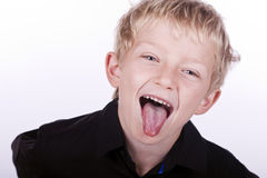 Boy sticks out tongue. A cheeky young blonde boy sticks out his tongue Stock Images