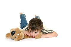 Boy on stomach isolated. Young boy laying on his stomach and looking off to his right, holding a toy dog; isolated on a white background royalty free stock images