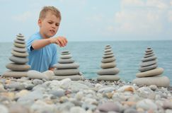 Boy and stone stacks on pebble beach Royalty Free Stock Photography