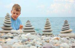 Boy and stone stacks on pebble beach Stock Photography