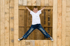 Boy stood in the window opening Stock Images