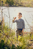 Boy Stopping to Smell Plant Along Shore of Lake Royalty Free Stock Photos