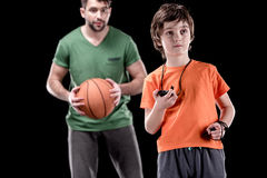 Boy with stopwatch controlling time with man holding basketball ball on black royalty free stock images