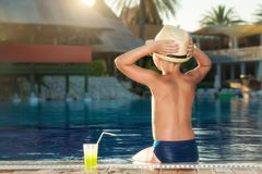 A boy in a straw hat with a cocktail in hand sitting on the pool stock photo