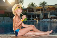 A boy in a straw hat with a cocktail in hand sitting on the pool stock photography