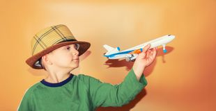 The boy in a straw hat holds a passenger plane, the concept of freedom and travel.  royalty free stock image