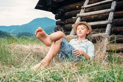 Boy in straw hat lies in hay near the barn royalty free stock photo