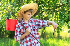 Boy in straw hat looking at caught fish Royalty Free Stock Photo