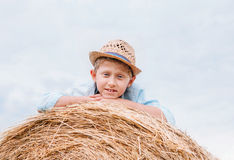 Boy in straw hat lying on the haystack Stock Photo