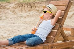 The boy in the straw hat and sunglasses lying on the wooden sun lounger on the beach and drink fresh juice.Summer vacation. stock images