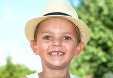 A boy in a straw hat without a tooth.Closeup portrait of. stock image