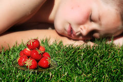 Boy and strawberries. Boy sleeping on grass with pile of ripe strawberries in foreground Royalty Free Stock Images