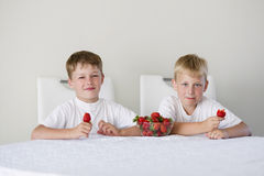 Boy with strawberries Stock Photos
