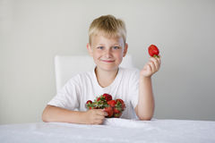 Boy with strawberries Stock Photo